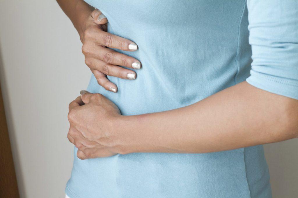 Вздутие живота и поясница болит: причины